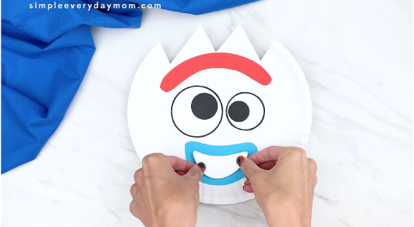 hands gluing on top part of Forky's mouth