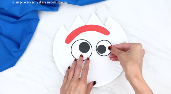 hands gluing on forky's eyes to paper plate