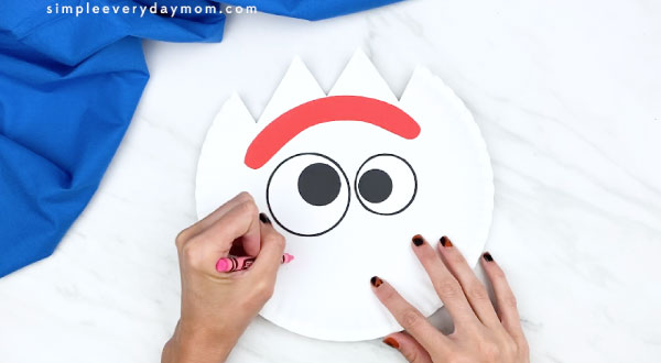 hands coloring in Forky's cheeks on paper plate