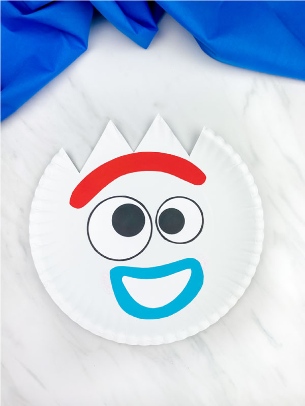 happy paper plate forky craft on marble background with blue fabric
