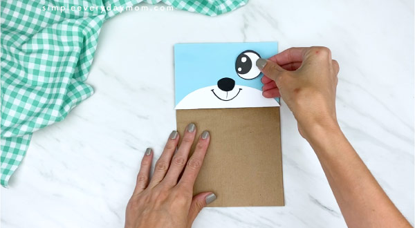hands gluing on eyes to paper bag mouse craft
