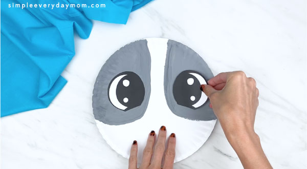 hands gluing eyes onto gray parts of paper plate
