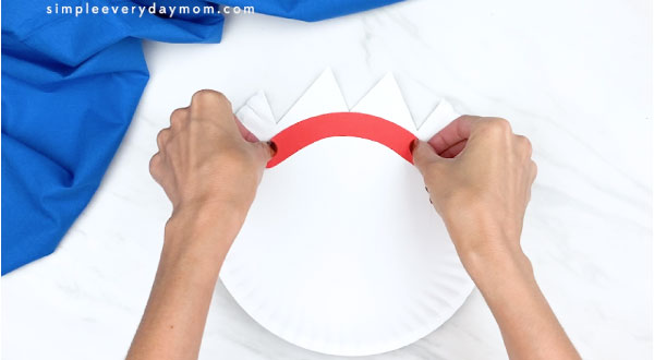 hands gluing on forky's eyebrows to paper plate