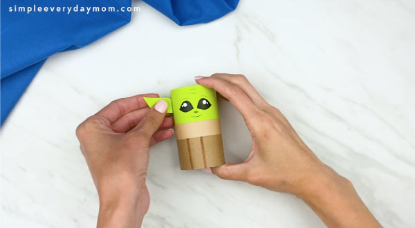 hands gluing on Yoda's ear to toilet paper roll