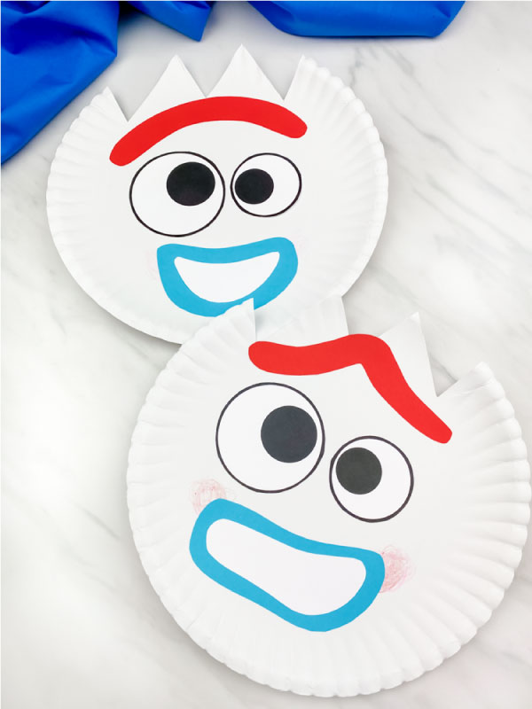 two paper plate forky crafts on marble background with blue fabric