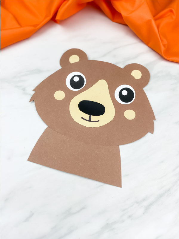 completed paper bear craft on marble background with orange fabric