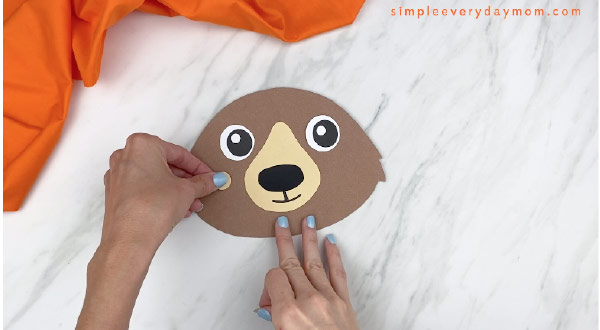 hands gluing on cheek to paper bear head