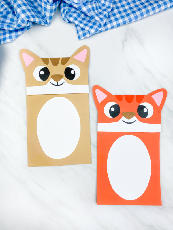 brown and orange paper bag cat puppet on marble background with blue checkered fabric
