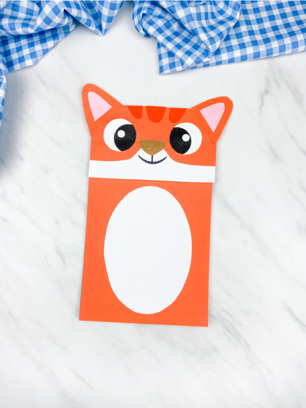 orange paper bag cat craft on marble background with blue checkered fabric
