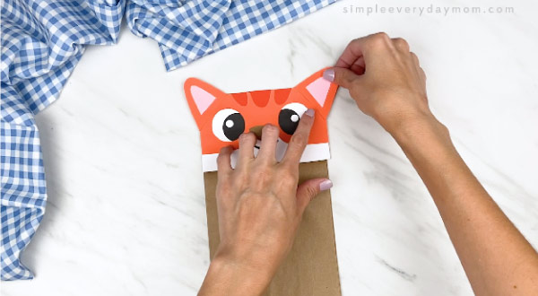 hands gluing finished ear onto cat paper bag puppet