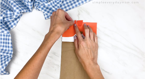 hands gluing on stripes on paper bag cat craft