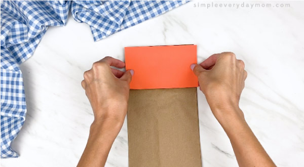 hands gluing on orange paper to top of brown paper bag