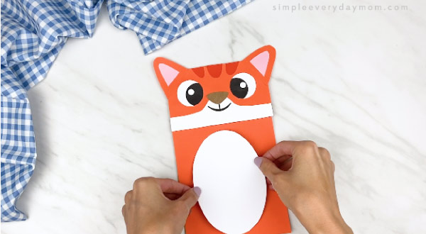 hands gluing on white belly onto cat paper bag puppet