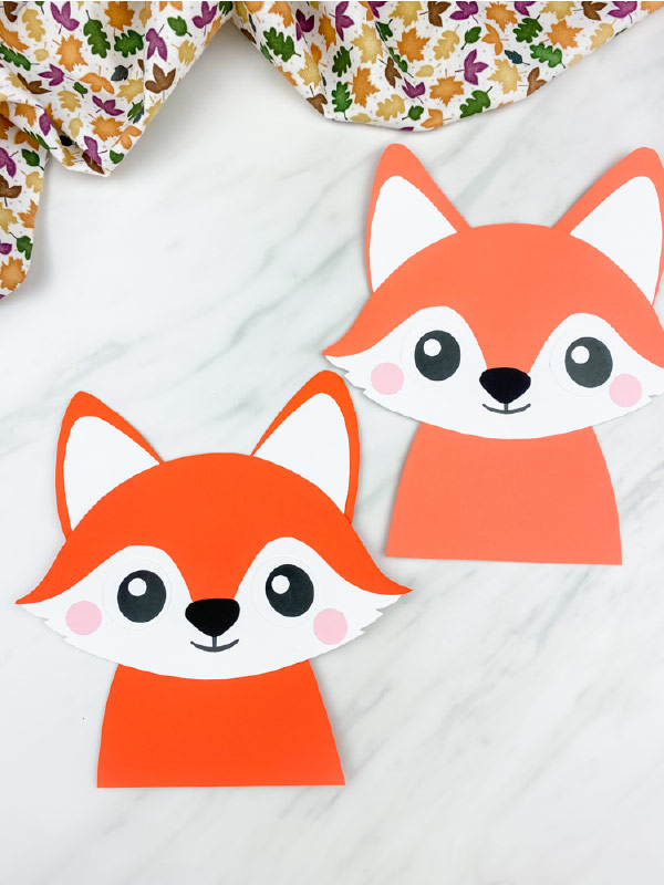 closeup image of two paper fox crafts  on marble background with leaf print fabric