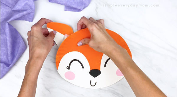 hands taping paper plate fox ear to back of paper plate