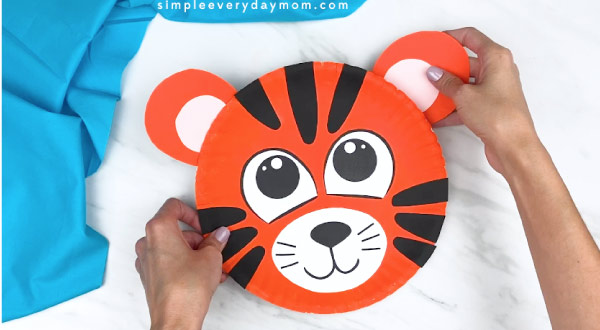 hands gluing tiger ear to back of paper plate tiger