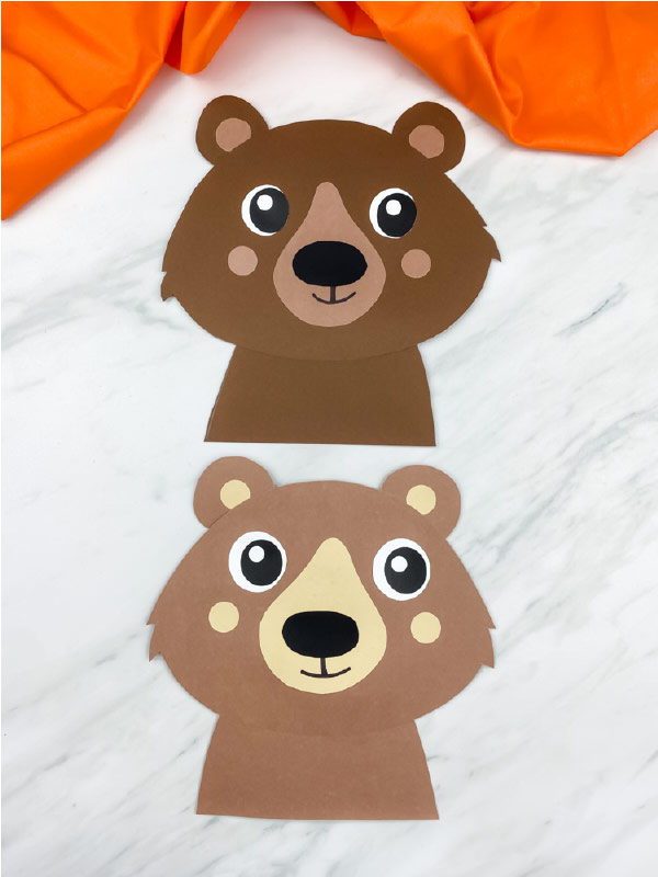 two completed paper bear crafts on marble background with orange fabric. Top bear is dark brown, bottom bear is light brown