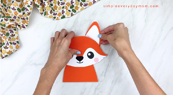hands gluing on completed fox to ear to back of fox head