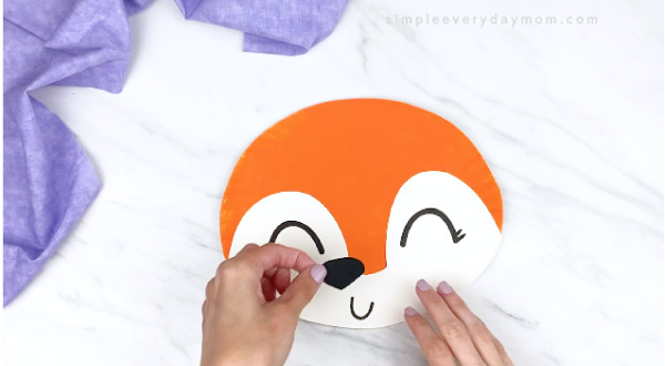 hands gluing black nose onto orange paper plate fox