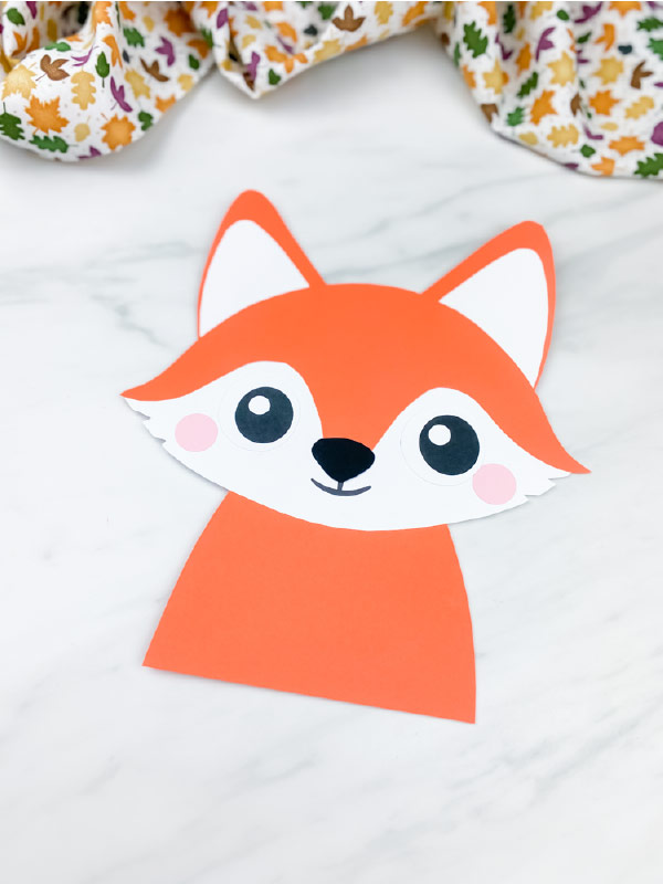 closeup image of one paper fox crafts  on marble background with leaf print fabric