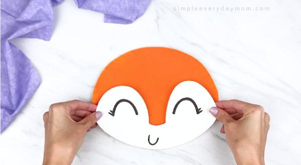 hands gluing fox face onto orange paper plate