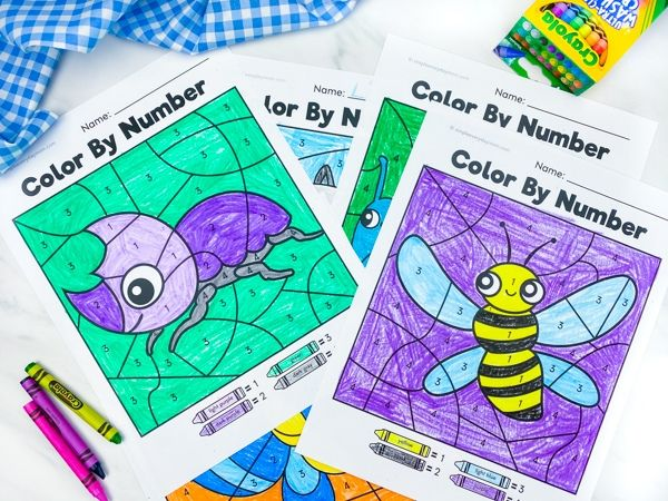 stack of bug color by number worksheets on marble background with crayons