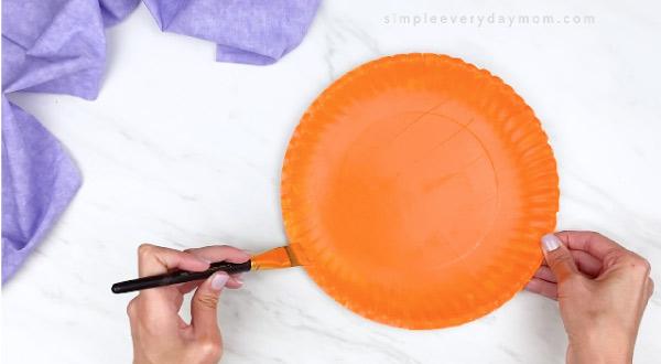 hands painting paper plate orange