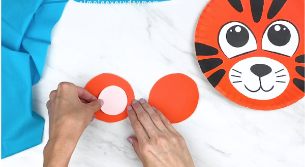 hands gluing on pink paper inner ear to orange outer ear
