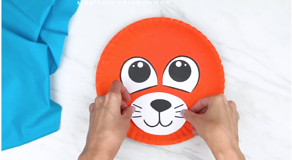 hands gluing on paper muzzle on orange paper plate