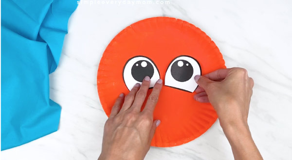 hands gluing on paper eyes onto orange paper plate