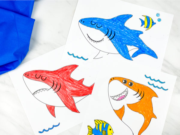 red, blue and orange shark coloring pages on marble background with blue fabric