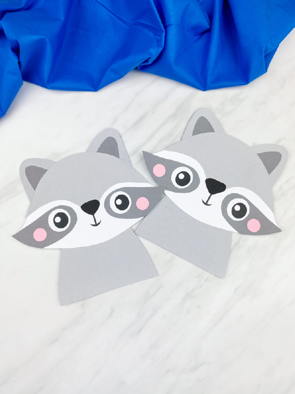 two completed paper raccoon crafts on marble background with blue fabric