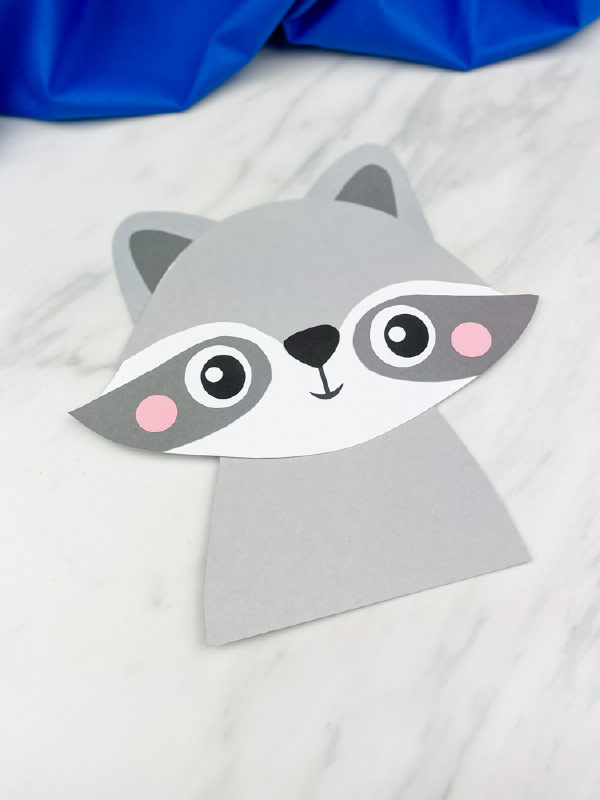 one  completed paper raccoon crafts on marble background with blue fabric