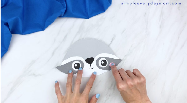 hands gluing on pink cheek to paper raccoon craft