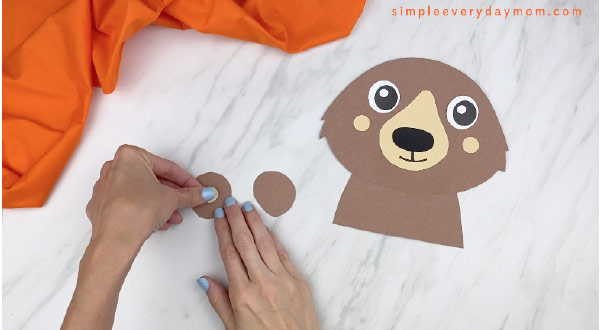 hands gluing on inner ear to outer ear of bear