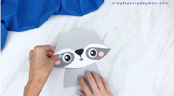 hands gluing on paper raccoon head to raccoon body