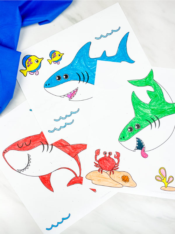 red, blue and green shark coloring pages for kids on marble background with blue fabric