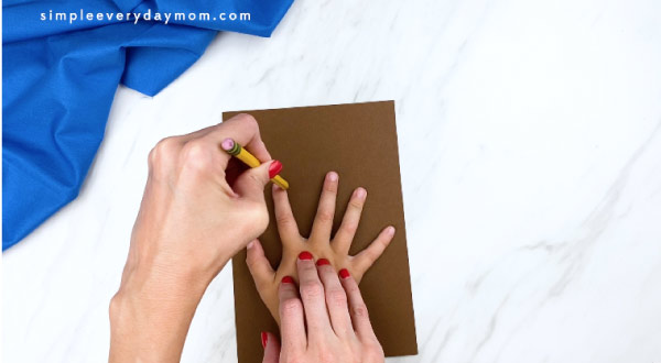 adult hand tracing child hand on brown paper