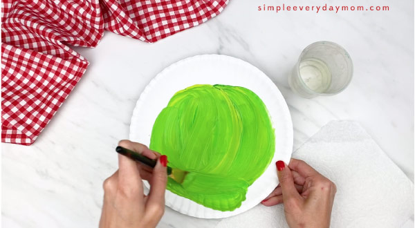 hands painting a paper plate green