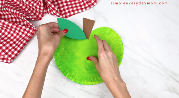 hands gluing on leaf on paper plate apple