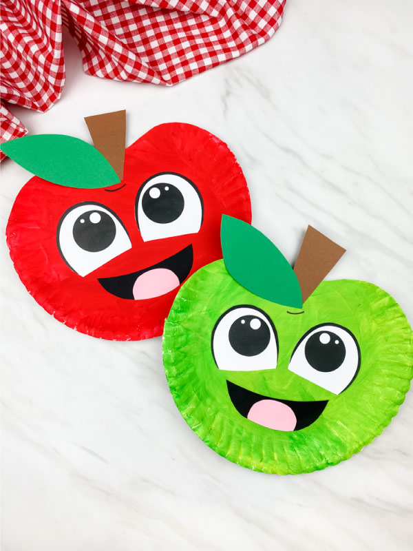 red and green paper plate apple craft on marble background with checkered fabric on top