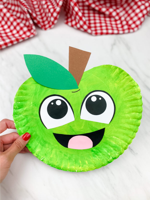 green paper plate apple craft on marble background with checkered fabric on top