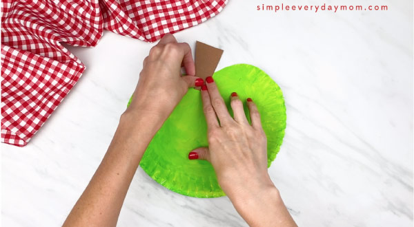 hands gluing on stem on paper plate apple