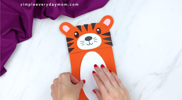 hands gluing white belly to tiger craft