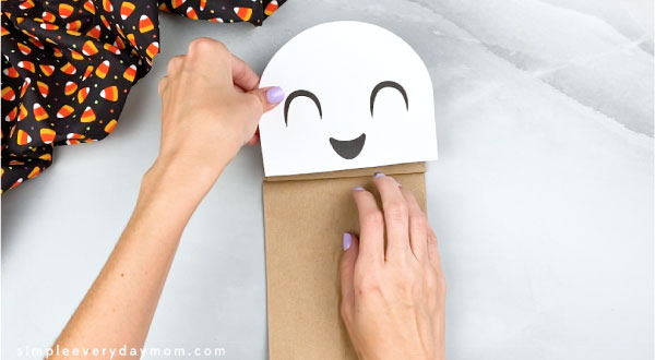 hands gluing ghost head onto paper bag