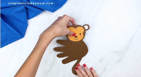 hands gluing tail to back of monkey handprint