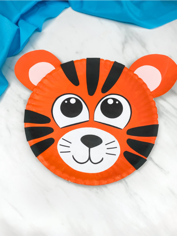 one paper plate tiger craft on marble background with blue fabric