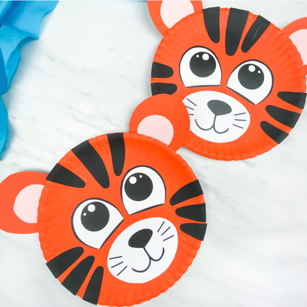 two paper plate tiger crafts on marble background with blue fabric