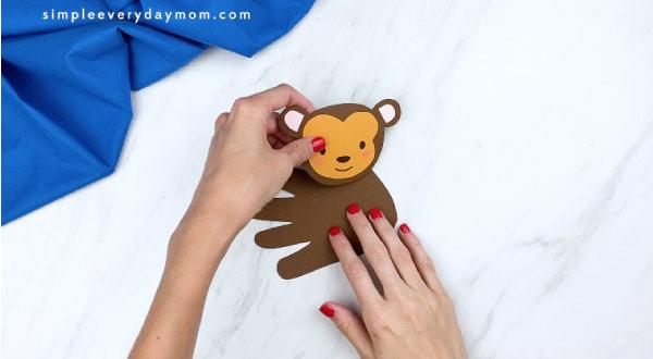 hand gluing monkey head to brown handprint
