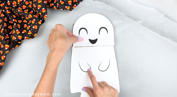 hands gluing paper bag ghost head on flap